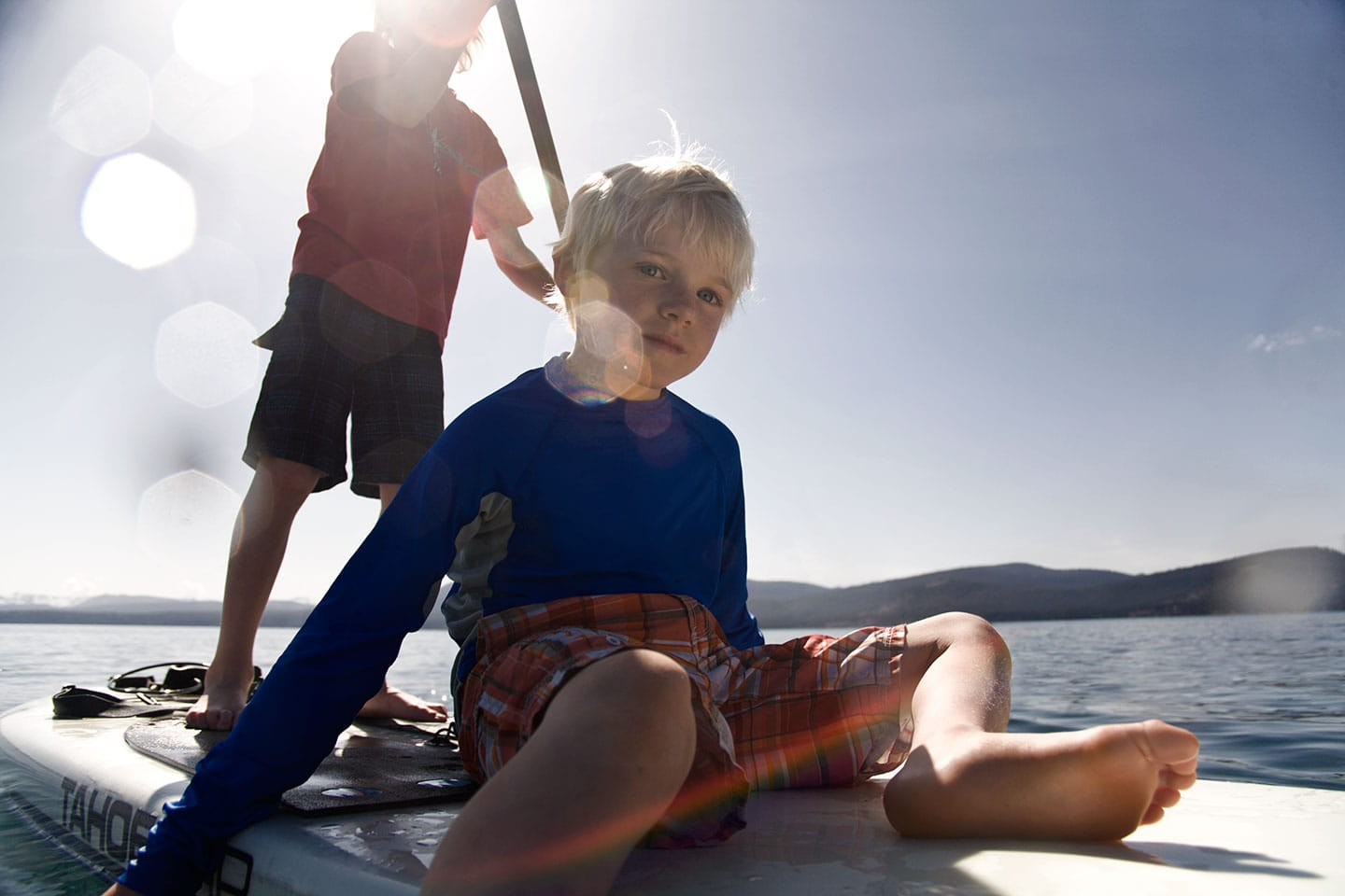 little boy sitting on a paddle board in lake tahoe