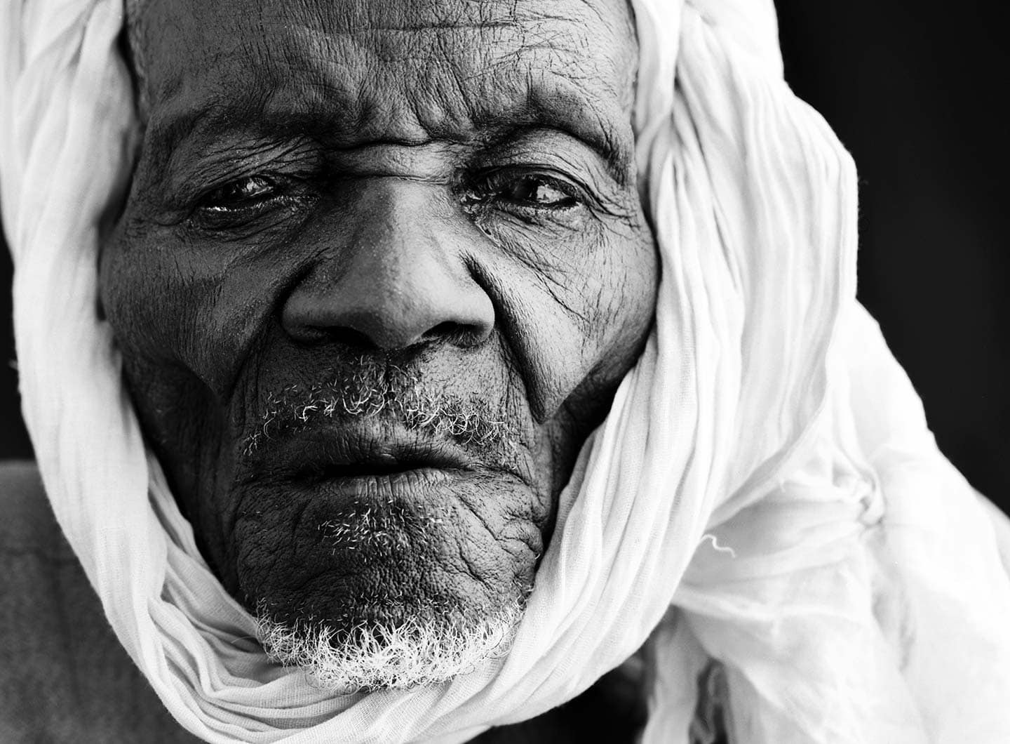 Rod Mclean - portrait of a old african man in white scarf