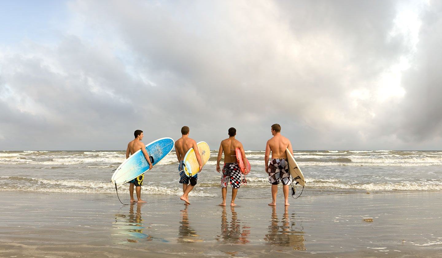 Back Image Four Men Entering Water With Surfboards Cloudy Beach