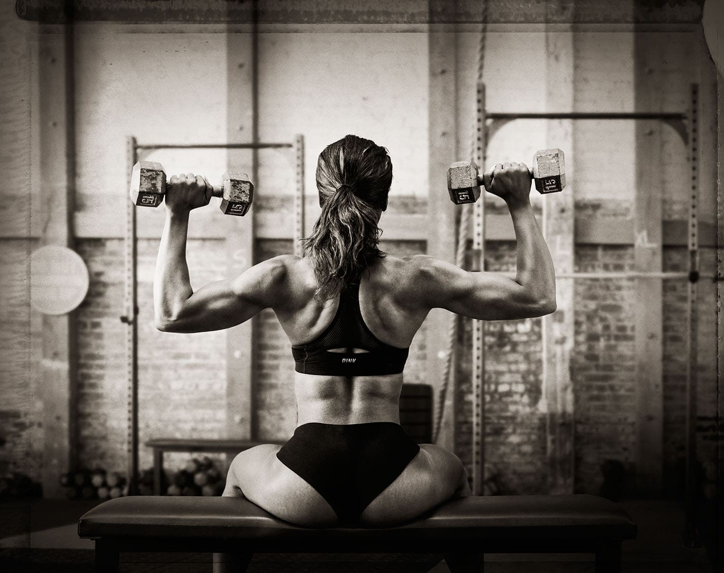 Black and White Image Behind Athlete Nicole Harris Doing Shoulder Press Two Piece Workout Apparel Chanel