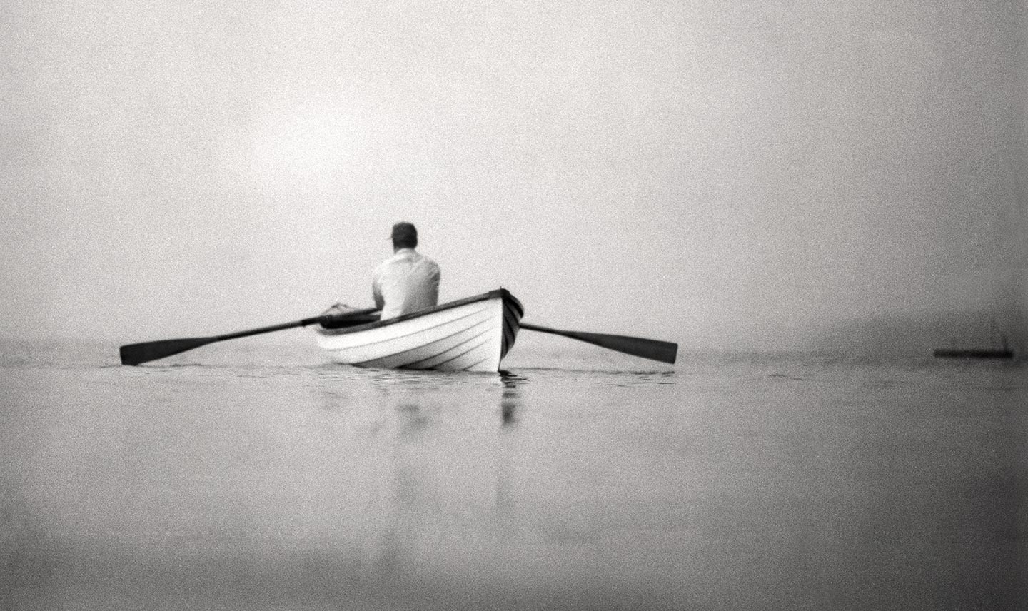 Black and White Image of Man Canoeing
