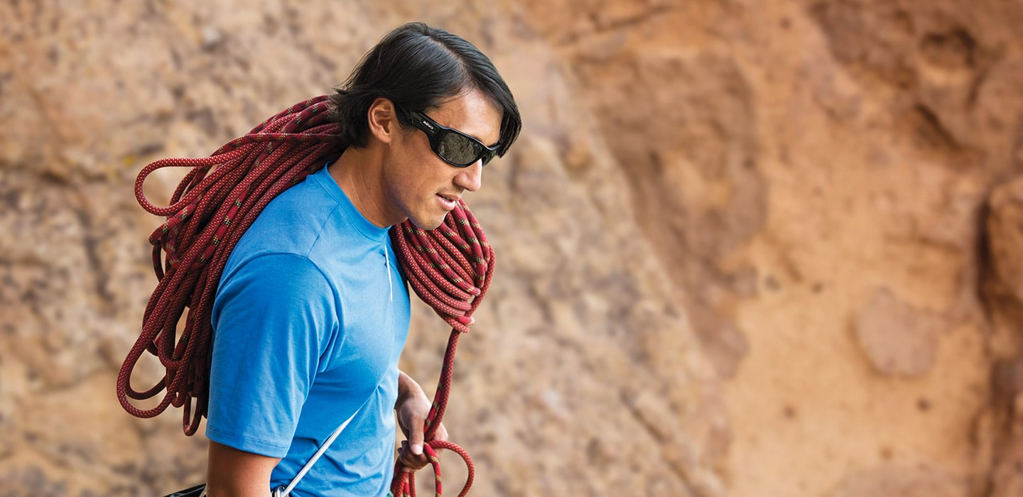 Climber Blue Shirt Sunglasses Carrying Rope on Shoulder