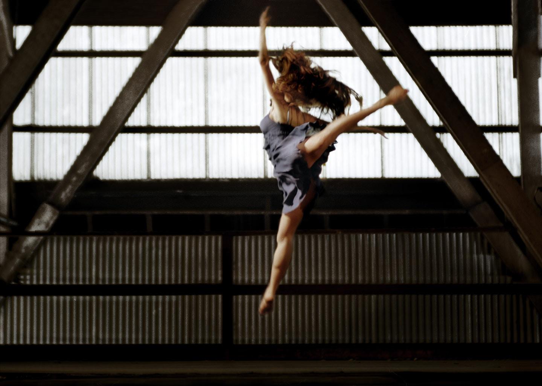 Dancer In Blue Blurred Profile Image Arabesque Jump Leg Raised Mid Air