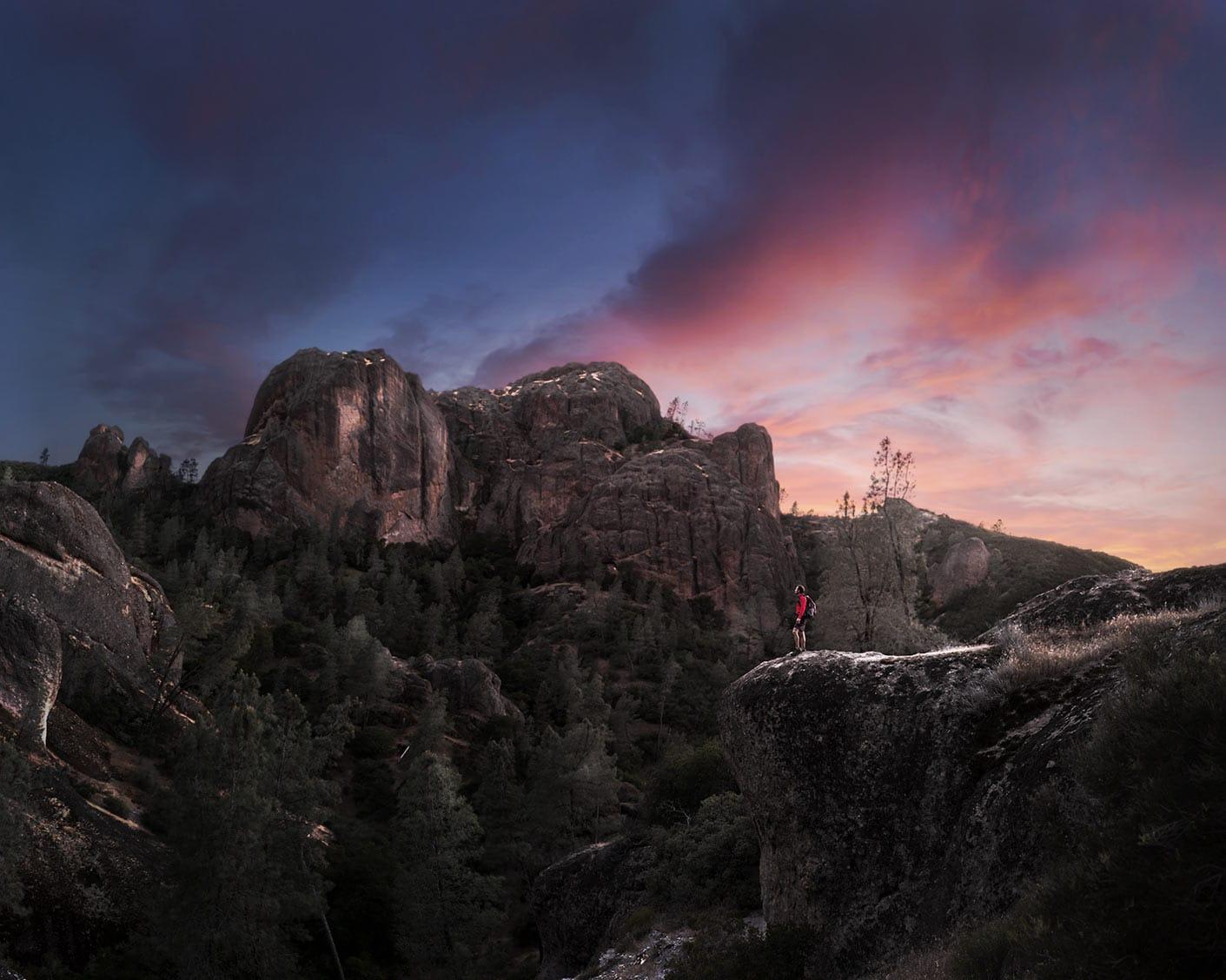 Hiker on Rocks Facing Left Faraway Shot Background Skies at Dusk