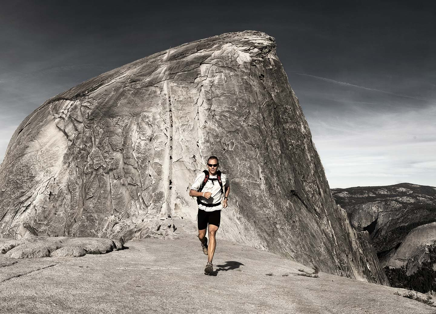 Image of Man in Black and White Sports Apparel Running with Grey Cliff in Background