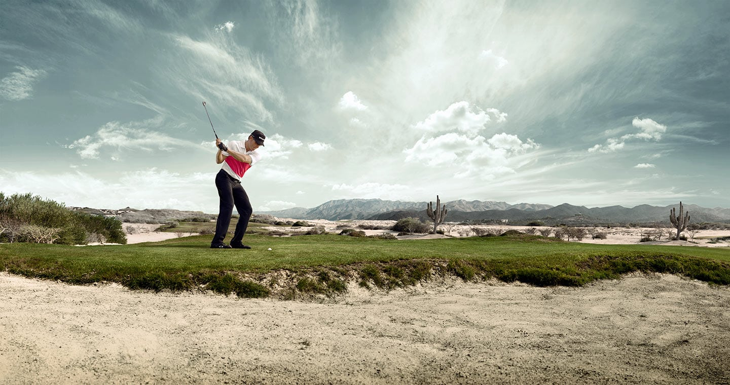 Image of Man in Mid Golf Swing on Golf Range Against Background of Bright Grey Skies