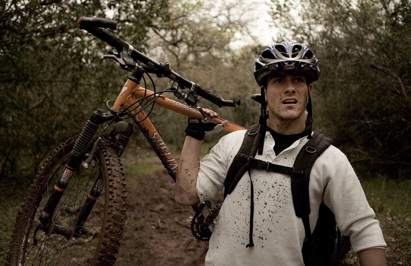 Image of Man in White Shirt with Biking Apparel Lifting Bike Behind Him Against Background of Forest