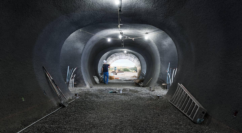 Image of Worker Walking Away Inside Lit Inner Cave