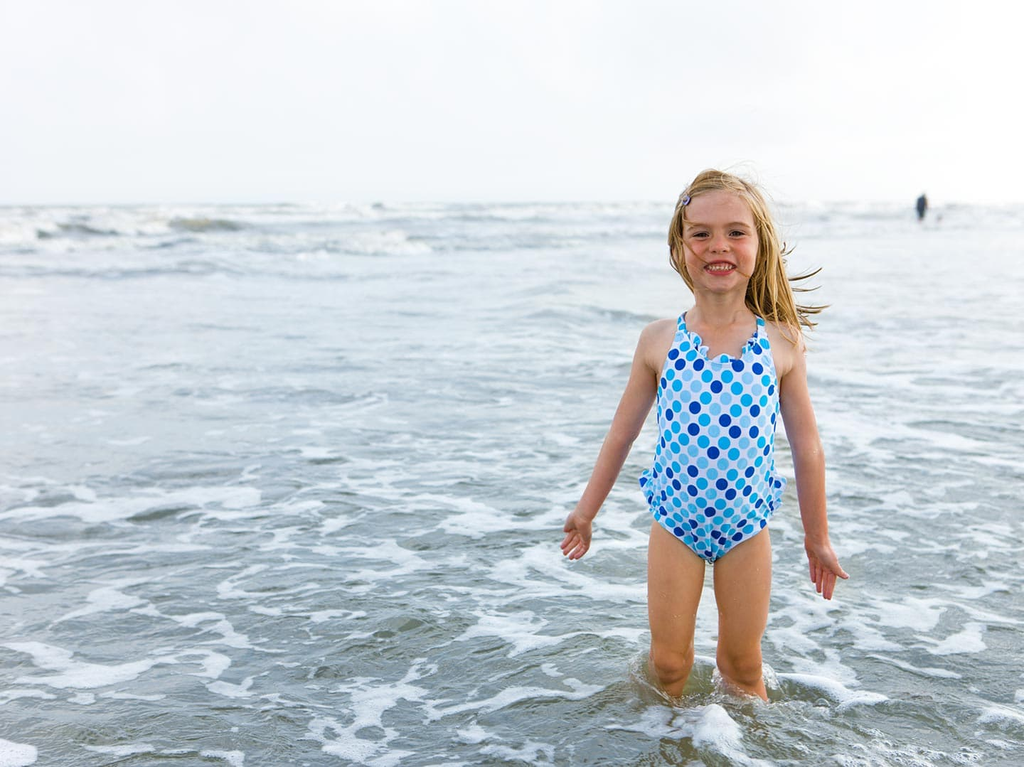 Little Girl at Beach in Swimsuit Smiling in Water
