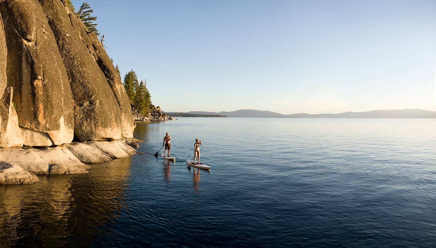 Man And Woman Standing on Surf Kayaks Paddling on Blue Water with Background of Blue Skies Cliff