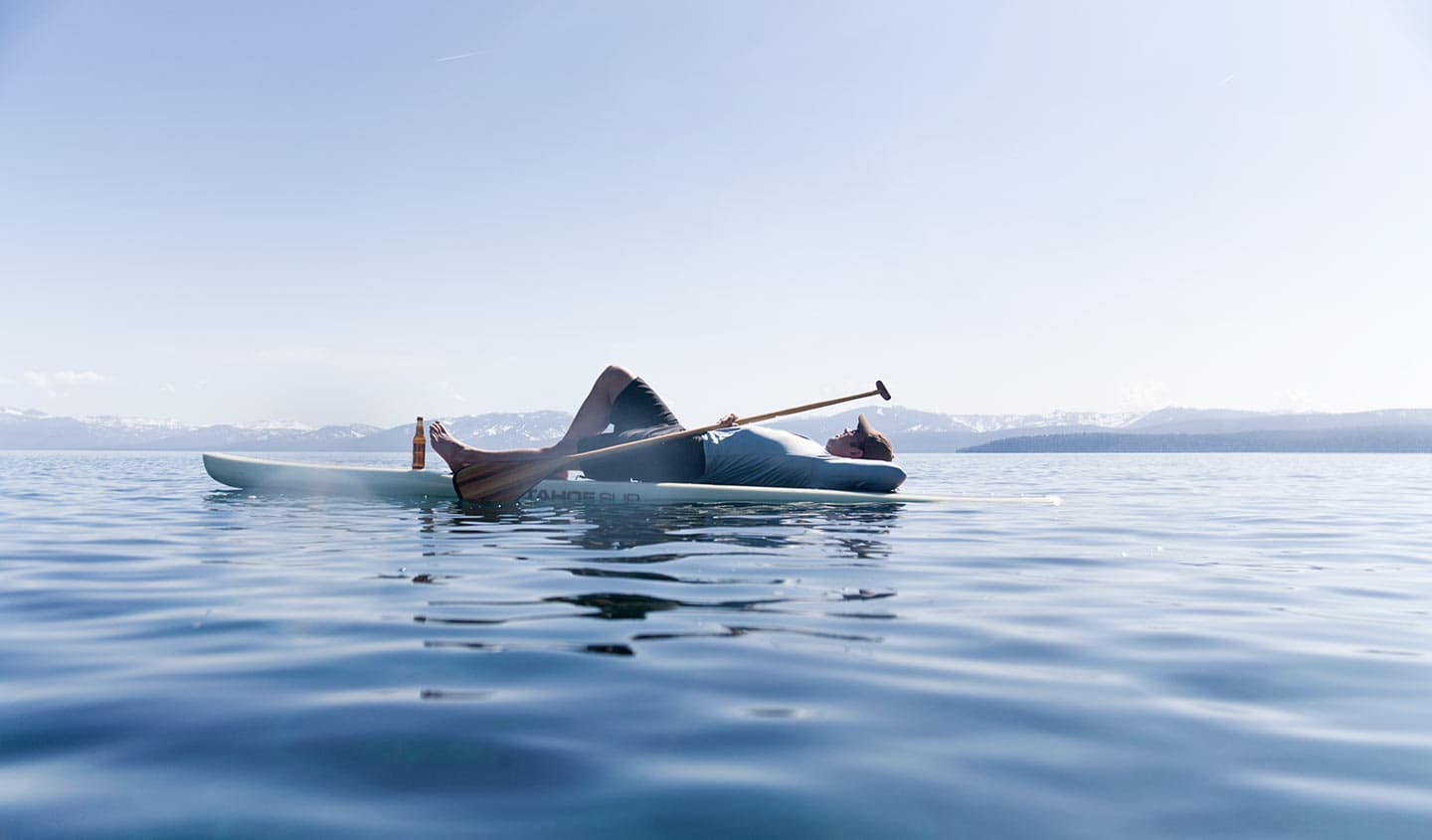 Man Relaxing Lying Down Kayak on Blue Water