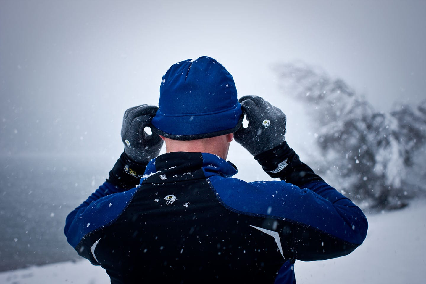 Man Wearing Blue Black Athletic Apparel Shot Behind Adjusting Hat Winter Snow