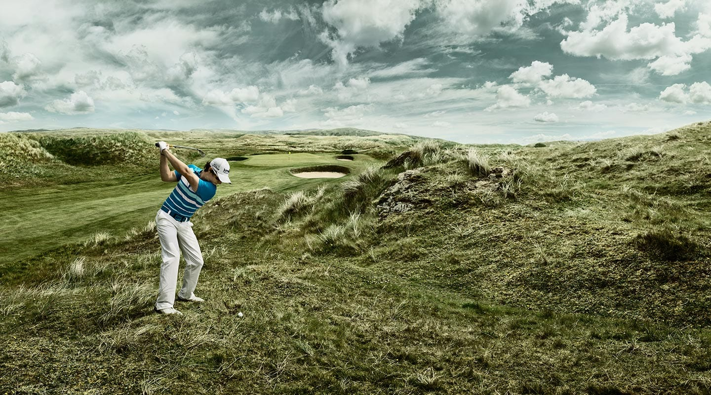 Man in Striped Shirt White Pants Mid Golf Swing Green Field Grey Skies Clouds