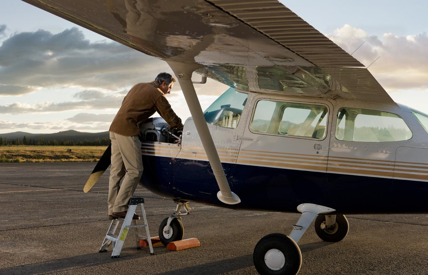 Man on Step Stool Fixing Private Plane