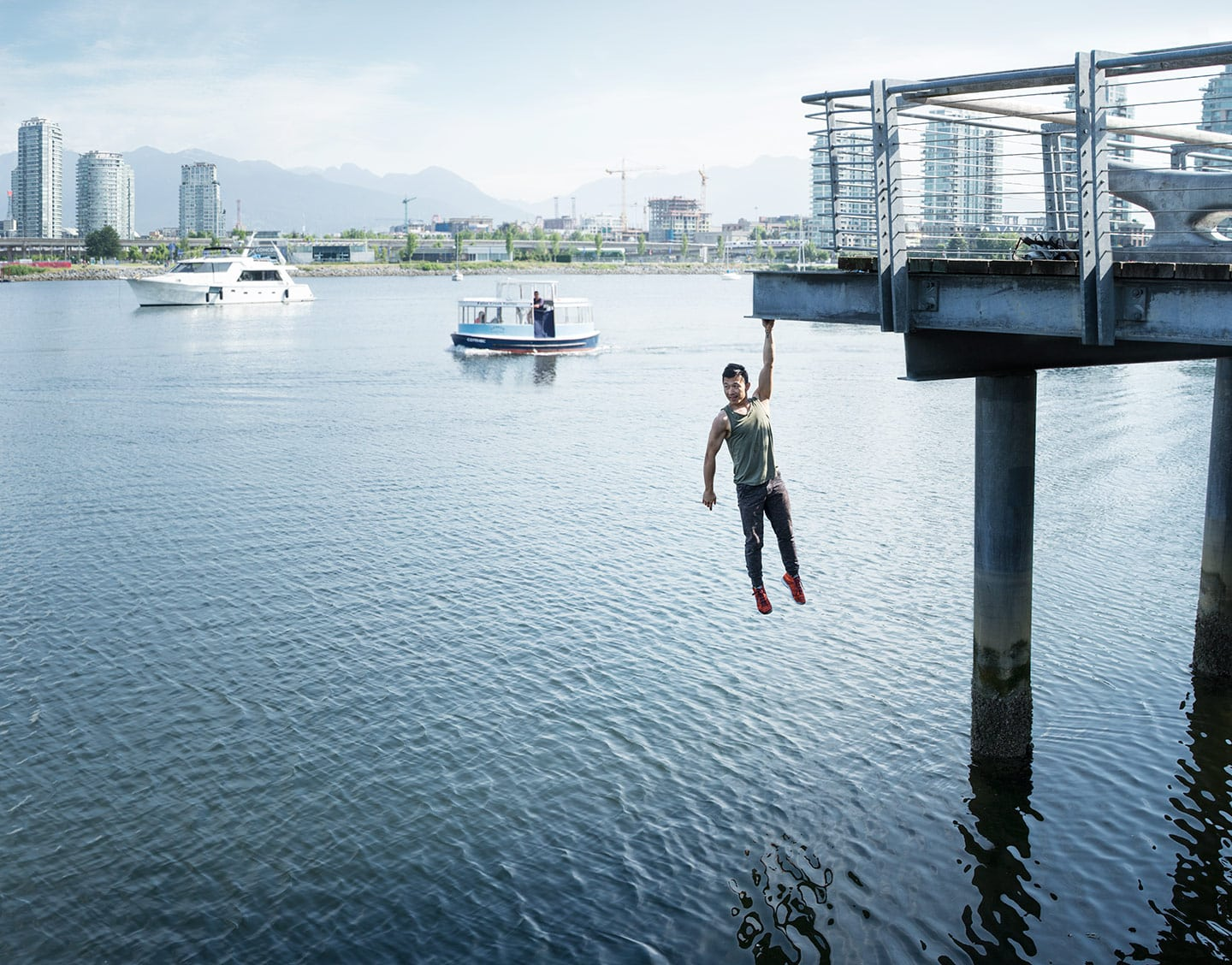 Parkour Athlete Hanging Over Blue Water Front Image City Skyline