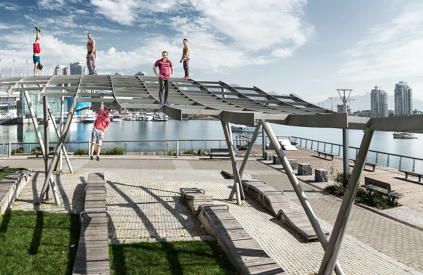 Parkour Athletes Pose for Image at Park on Scaffolding Bright Skies Handstand