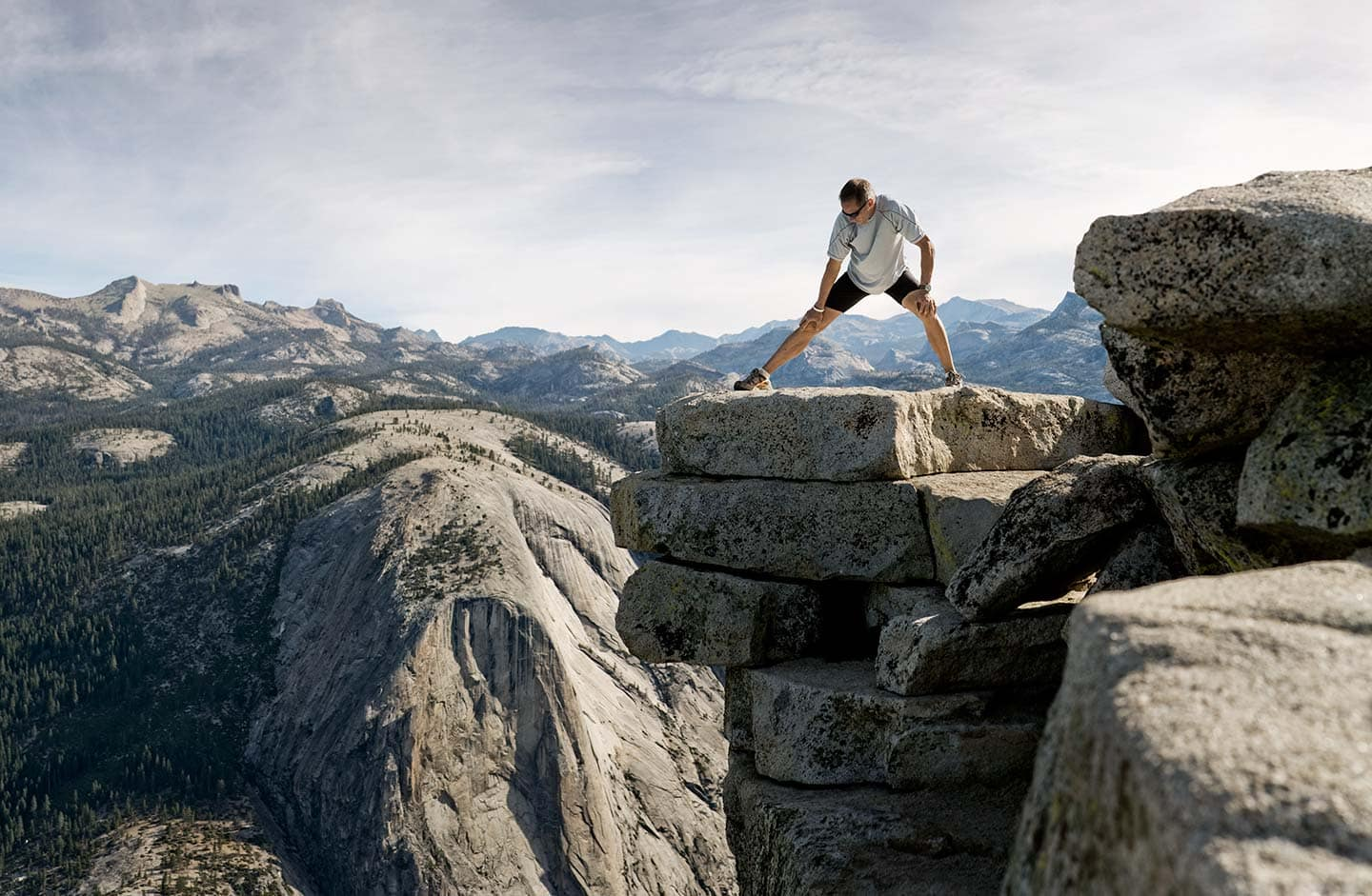 Runner in Black and White Athletic Apparel Stretching Over Rocks Against Background of Bright Skies