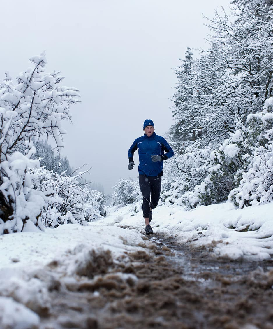 Runner in Blue Athletic Apparel Running in Cold Climate Against Snowy Background Front Perspective