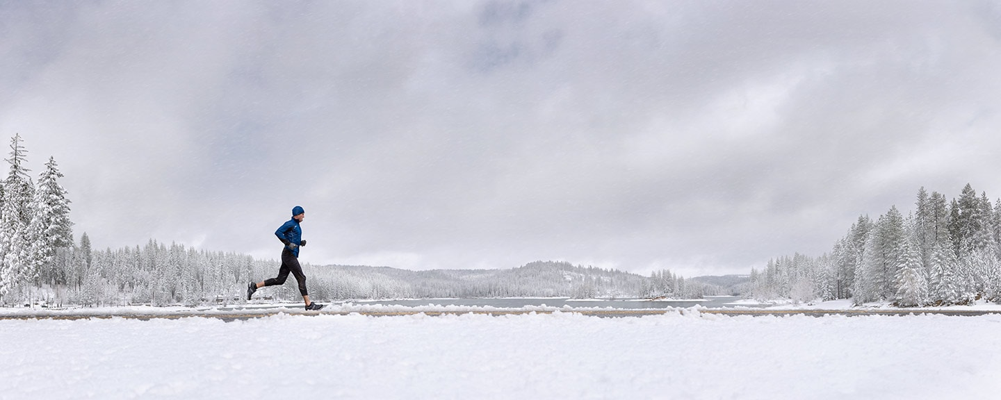 Runner in Blue Athletic Apparel Running in Cold Climate Against Snowy Background Profile Perspective