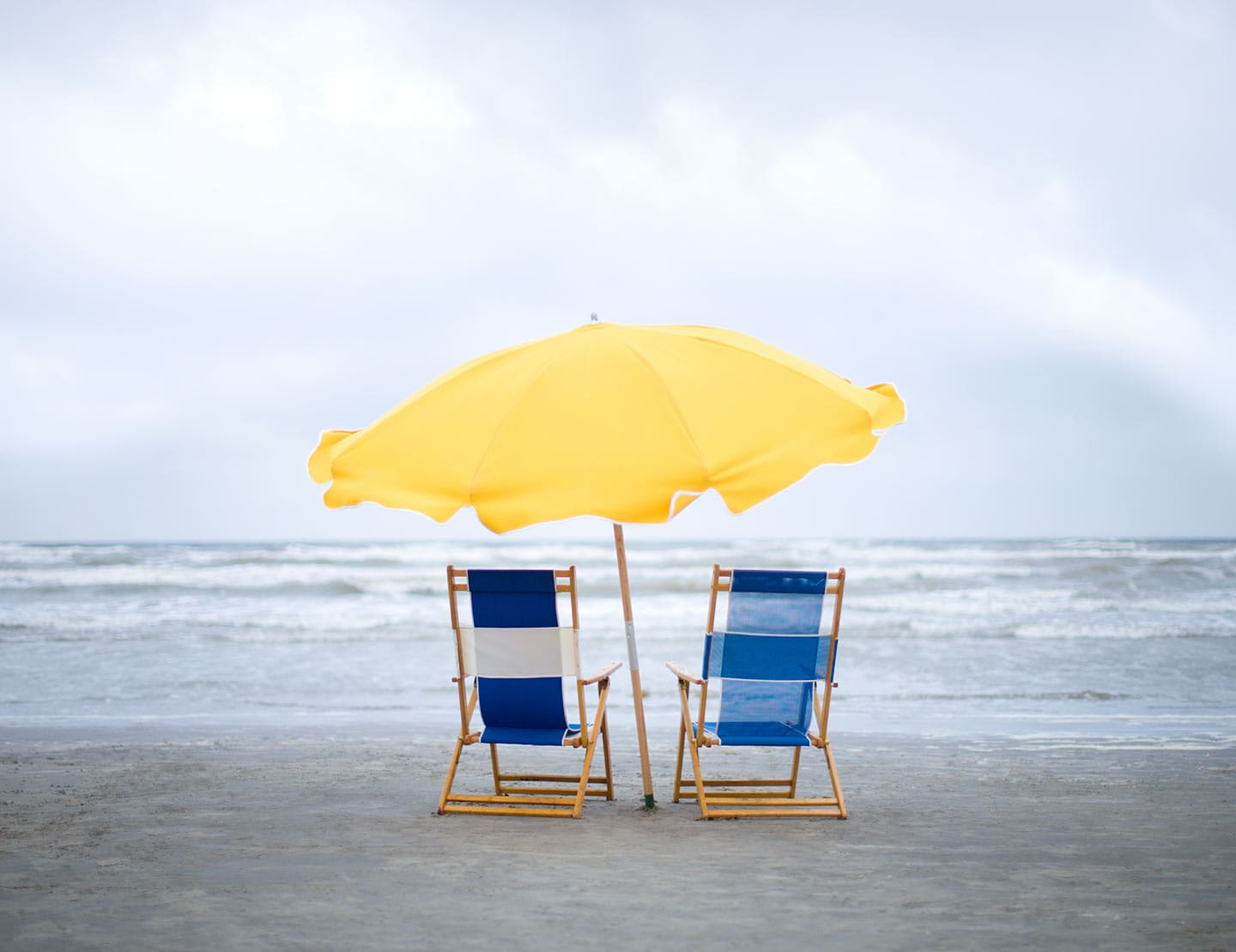 Two Blue Beach Chairs And A Yellow Sun Umbrella Facing Water Image  Perspective Behind