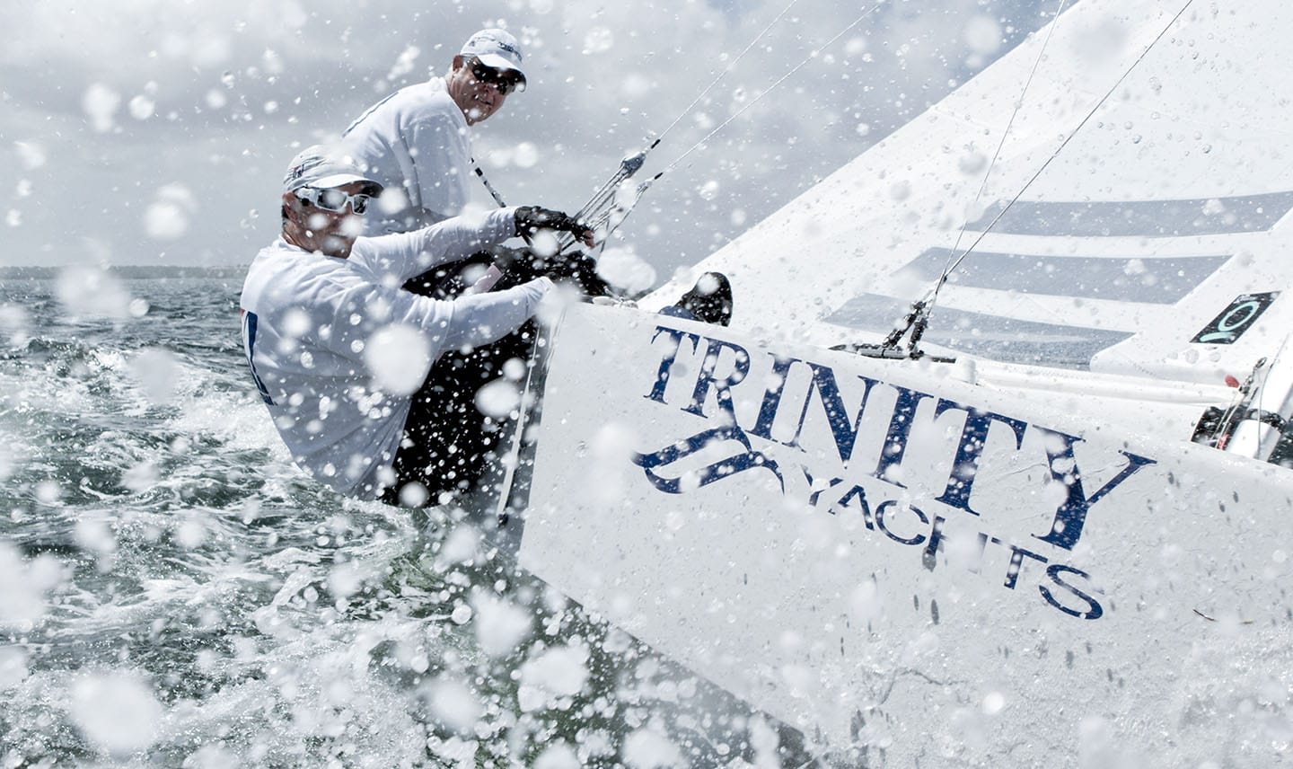Two Middle Aged Men in White Sailing Mid Splash Sailing Trinity Yachts