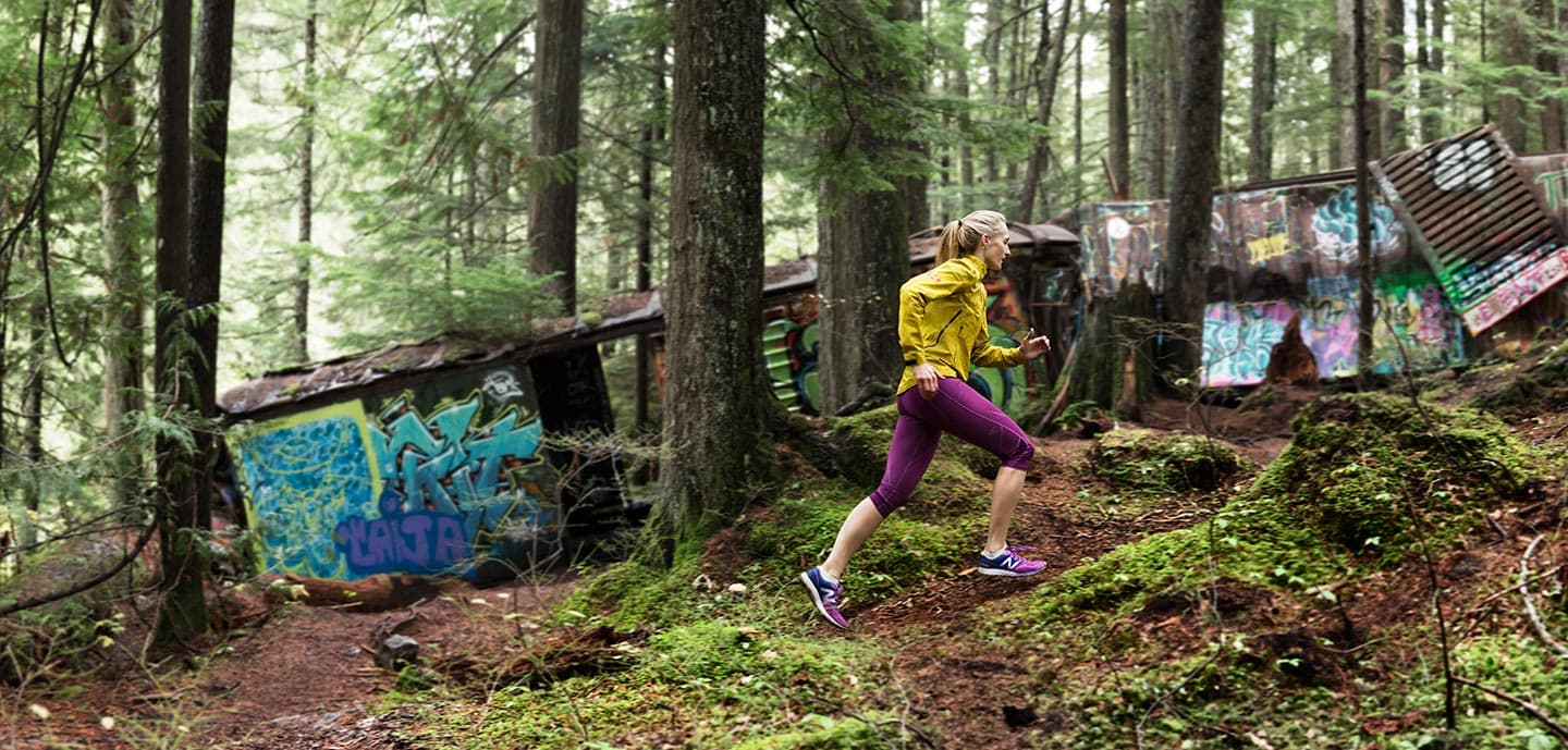 Woman in Yellow Jacket and Purple Capris Running In Forest Past Graffiti RodMcLean