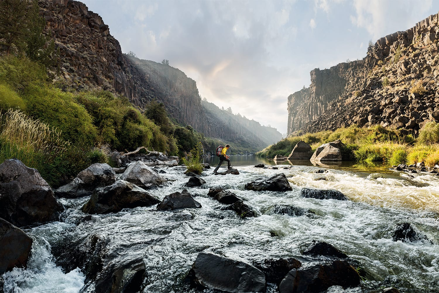 Active-Lifestyle-hiker-Jimmy-Chin-crossing-river-rocks-Rod-McLean