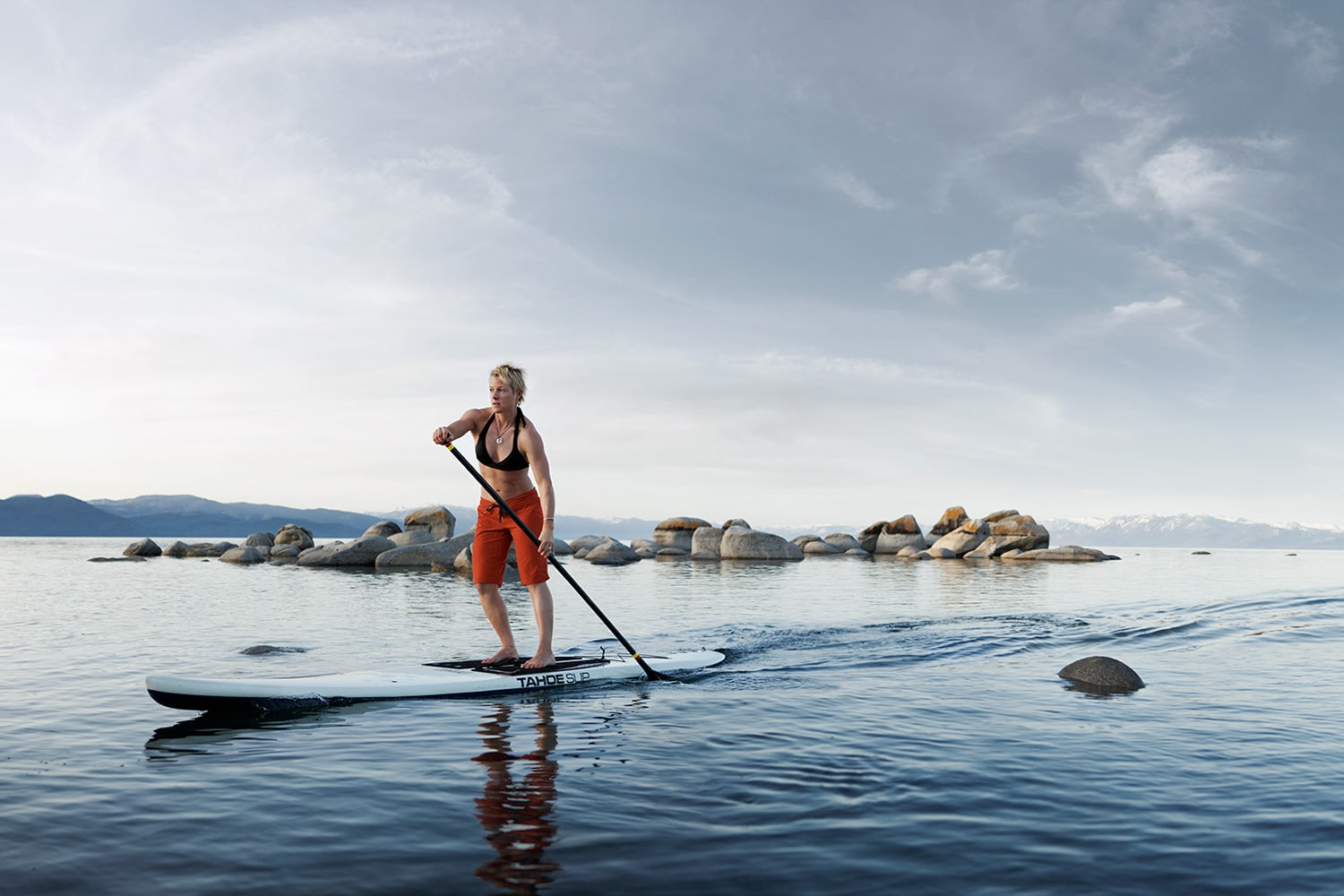 Active-Lifestyle-woman-paddle-boarding-on-lake-rocks-Rod-McLean