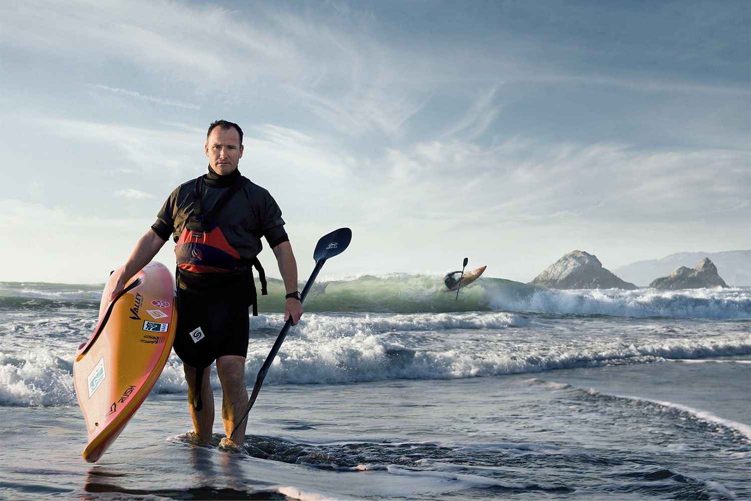 Athlete-Man-holding-a-kayak-and-paddle-at-the-beach-waves-Rod-McLean