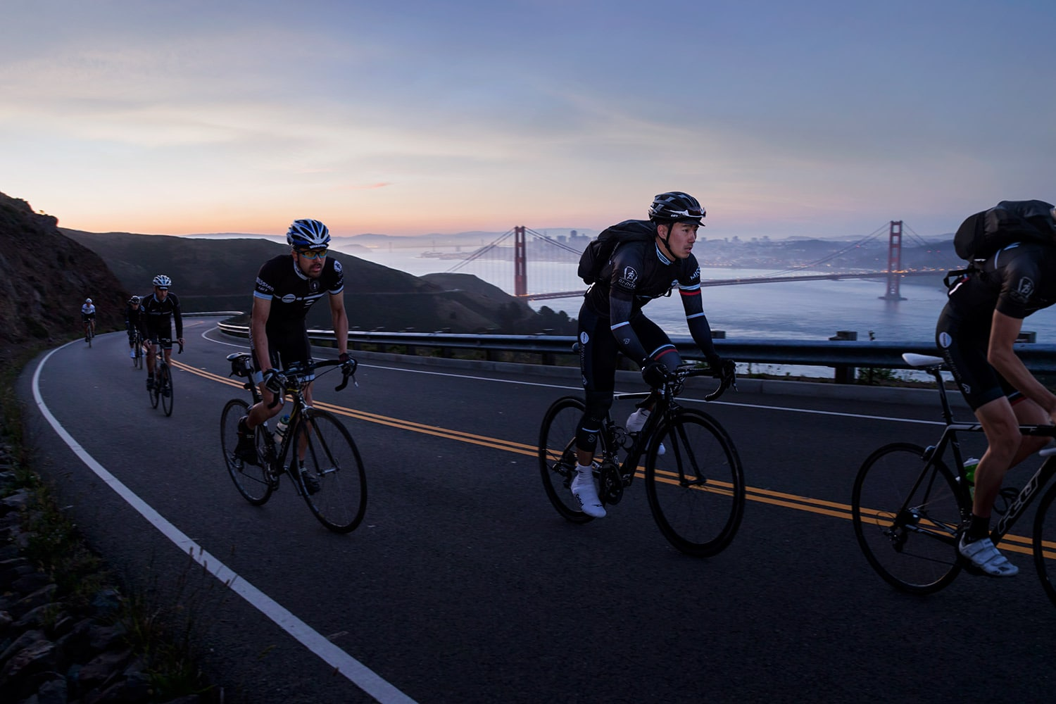 Athletes-Cyclists-ridding-up-hill-with-golden-gate-bridge-and-city-Rod-McLean