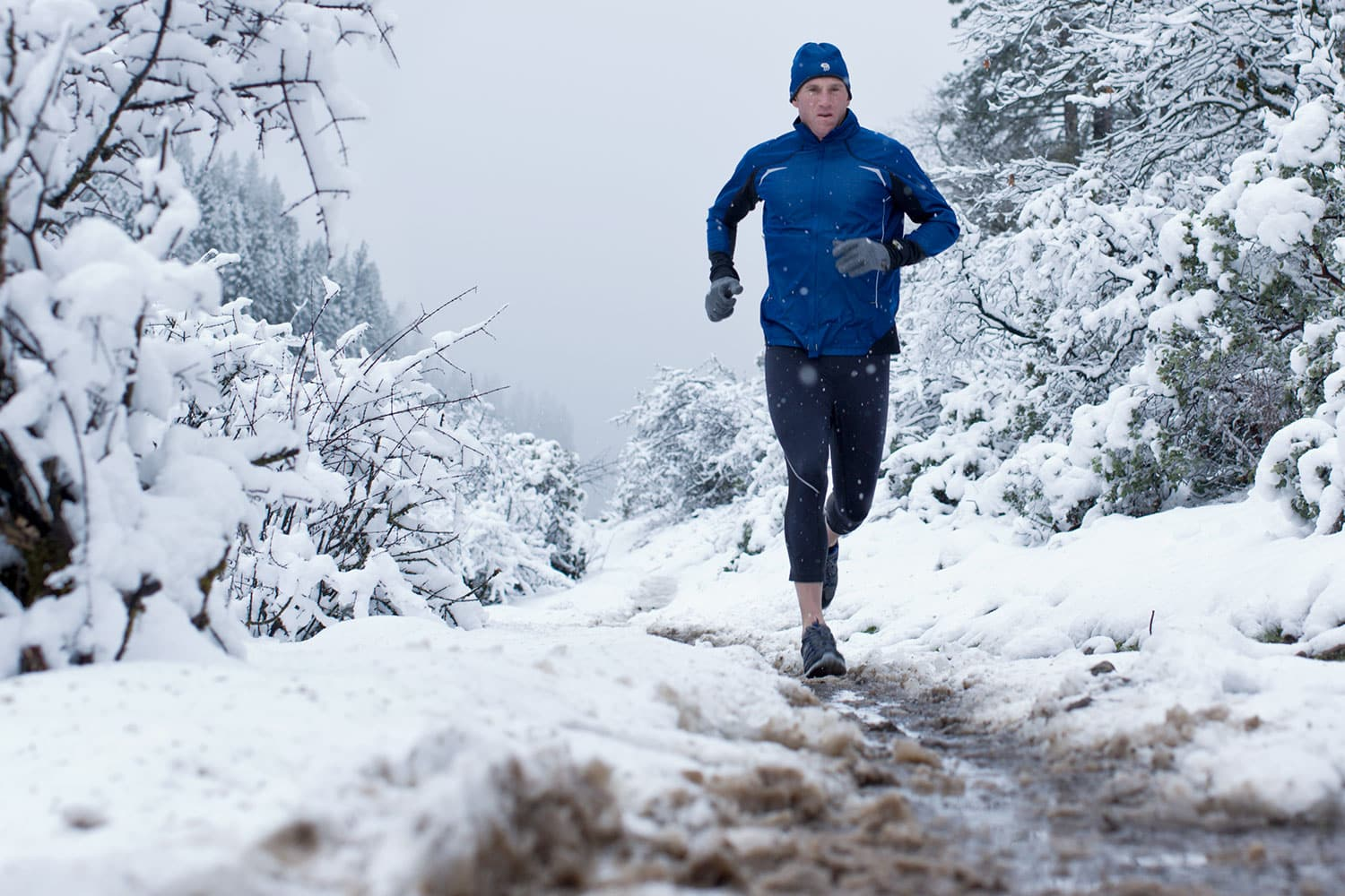Athletic-lifestyle-Man-running-on-muddy-path-in-a-snow-storm-Rod-McLean