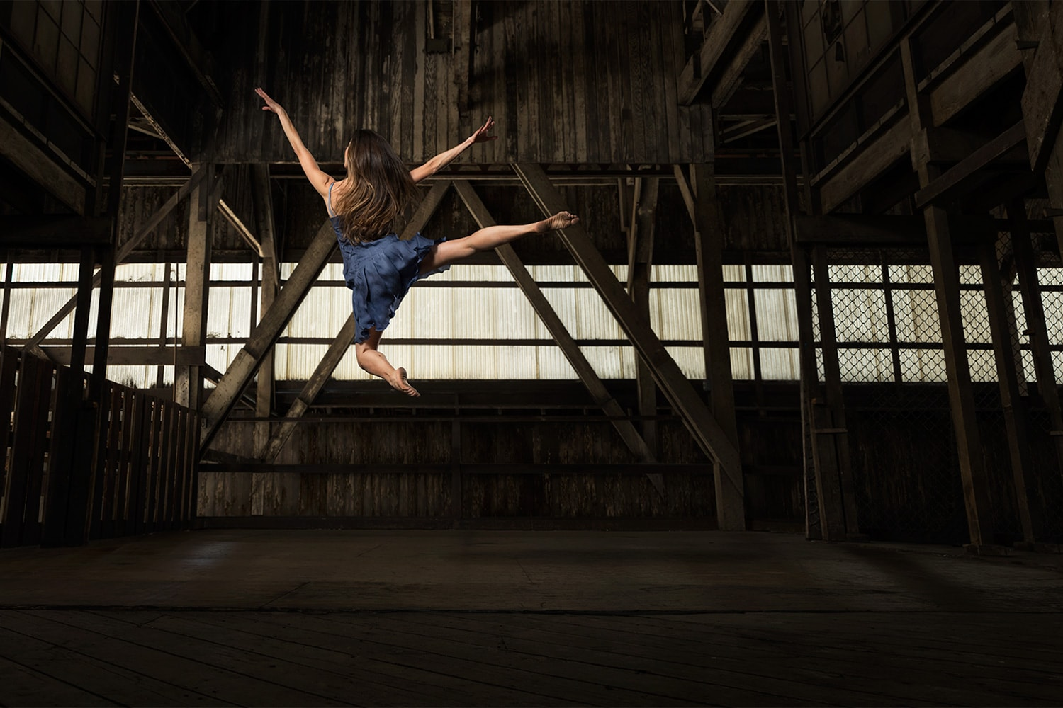 Female Ballerina Ballet jumping wearing a blue outfit dancing in a wood warehouse Photographer Rod McLean