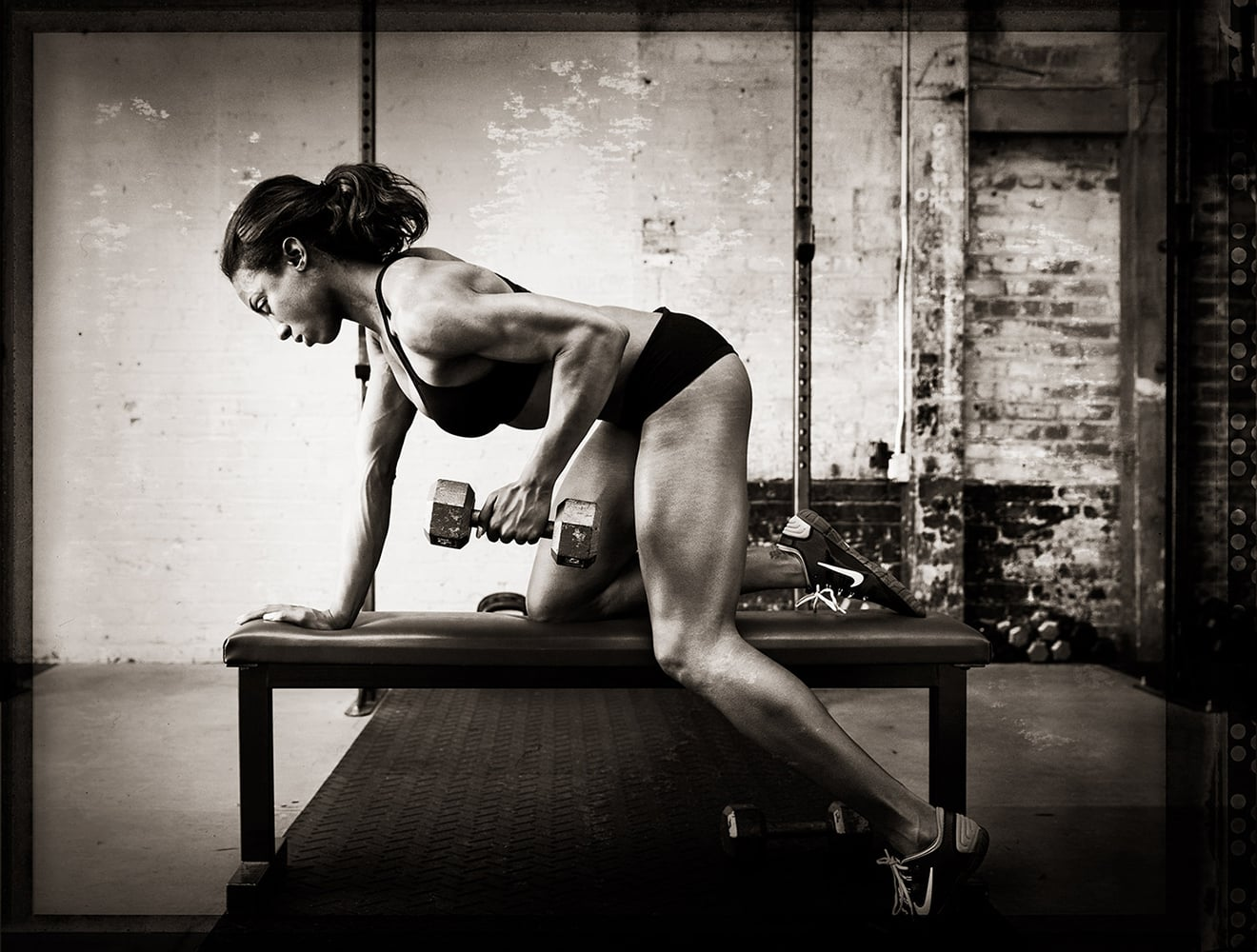 Female-athlete-working-out-with-weights-in-gym-Rod-McLean