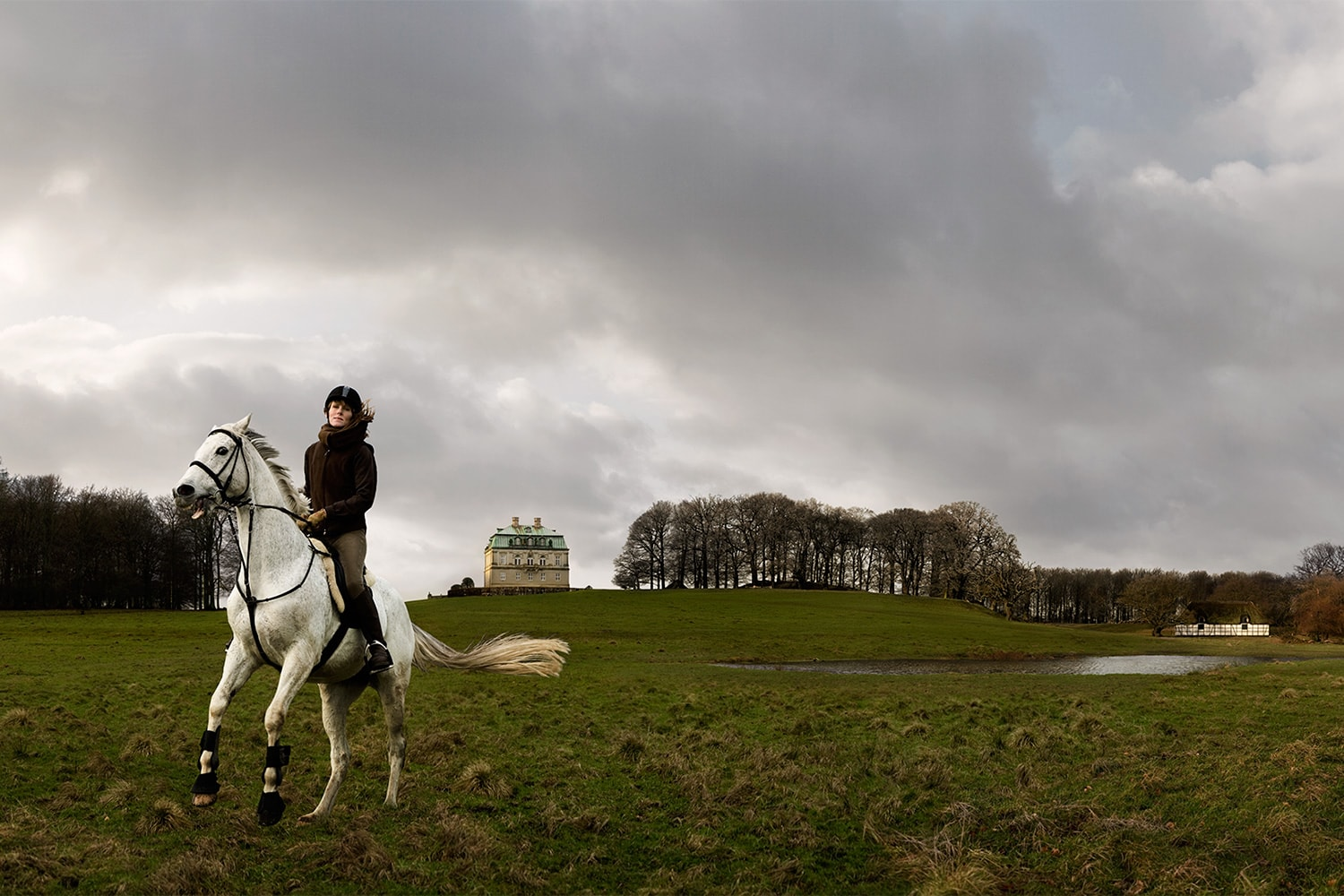Female-riding-white-horse-in-a-field-in-front-of-castle-Rod-McLean