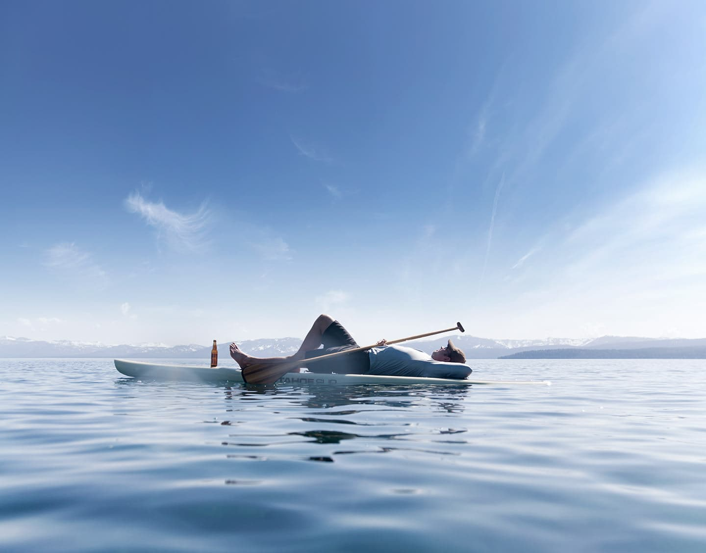 Man-laying-on-paddle-board-on-Tahoe-lake-with-mountains-Rod-McLean_G