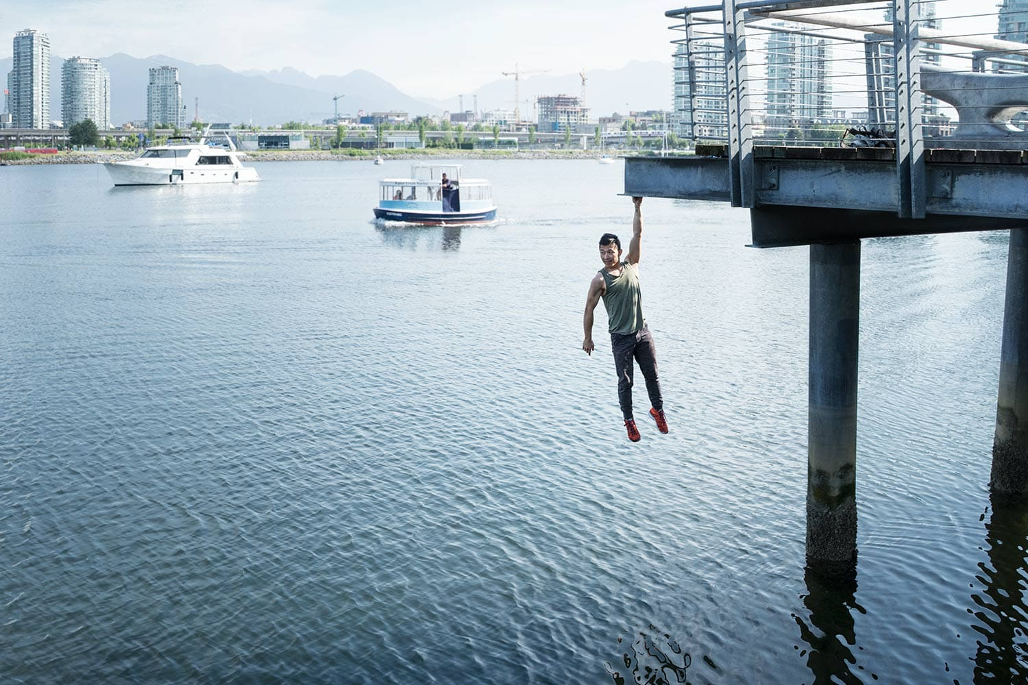 Parkour-male-Athlete-hanging-over-water-from-a-bridge-Rod-McLean