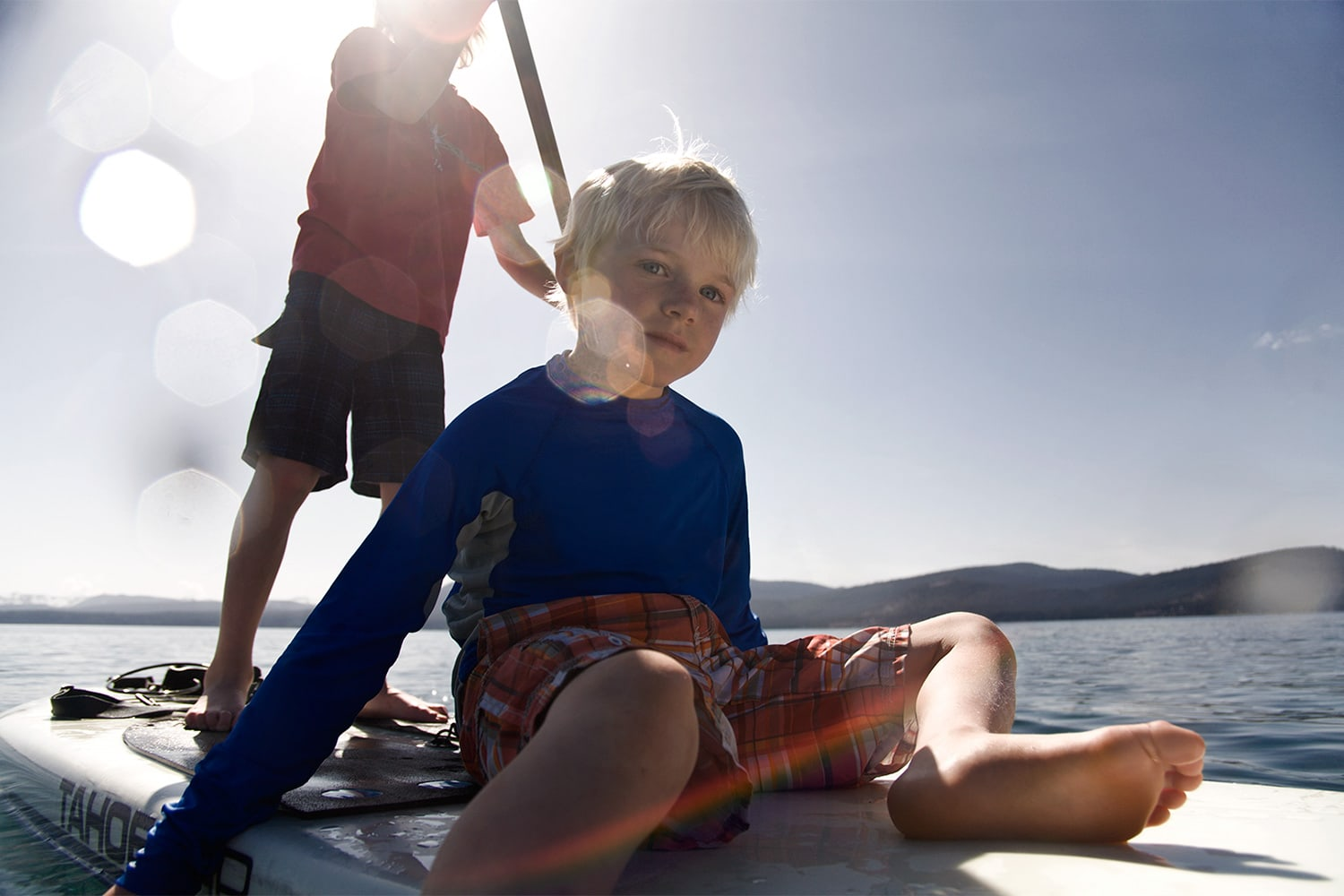 little-boy-sitting-on-a-paddle-board-in-lake-tahoe-Rod-Mclean