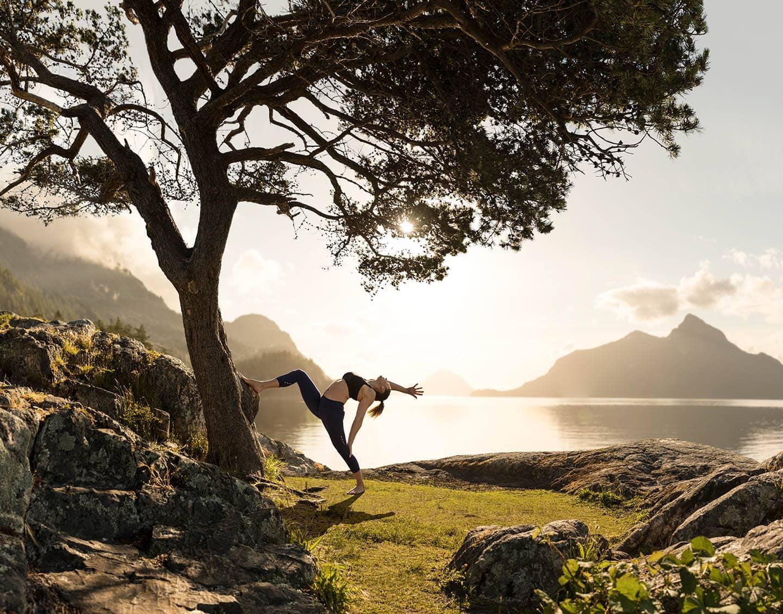 Women doing yoga backbend with sun near water